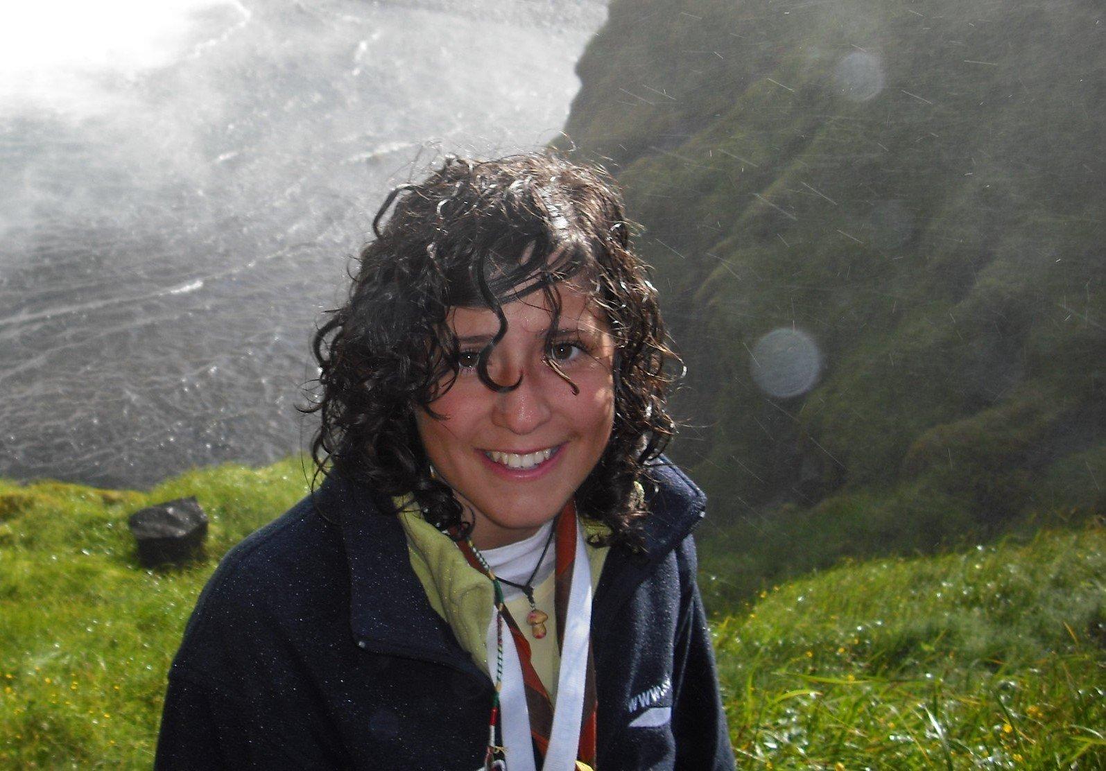 Chica empapada por la lluvia, con una chupa muy grande.