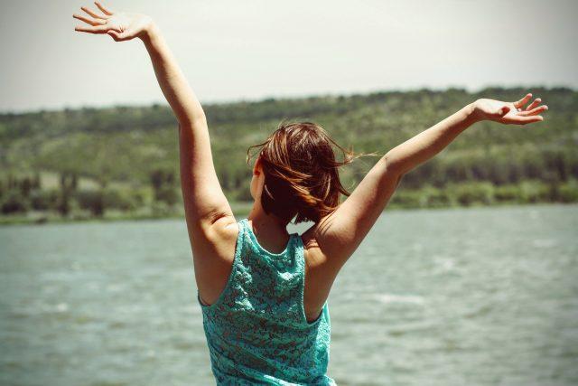 Mujer de espaldas feliz ante un lago.