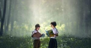 Un niño y una niña leen en el bosque.
