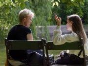 Dos chicas hablan en un banco en el parque.